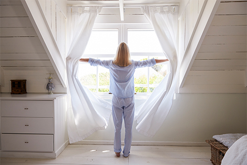 Woman Opening Curtains and Windows